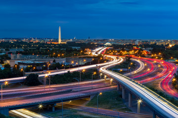 Fotomurales - Washington D.C. cityscape at dusk with rush hour traffic trails on I-395 highway. Washington Monument, illuminated, dominates the skyline.