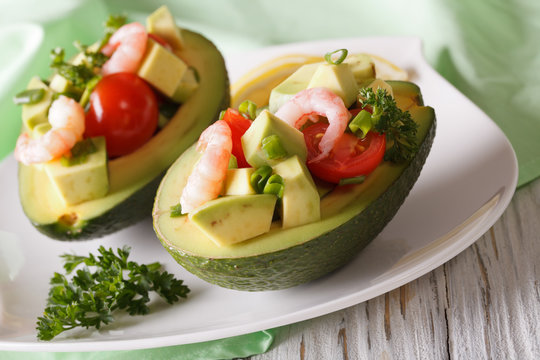 Avocado stuffed with shrimp close-up on a plate. horizontal
