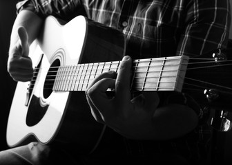 The young man playing an acoustic guitar in the studio.