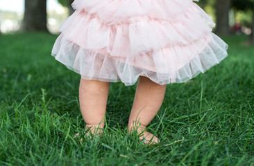 Little baby feet on fresh green grass outdoors