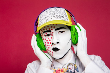 man in headphones listens to music.  dressed in the style of pop art. bright makeup