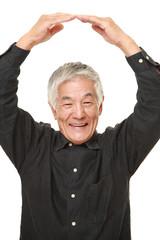 senior Japanese man making OK gesture