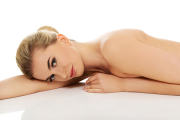 Beautiful young slim woman lying on belly.