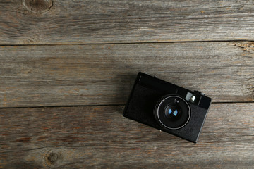 Old retro camera on grey wooden background