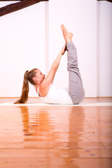 Woman practicing Yoga in a Studio.