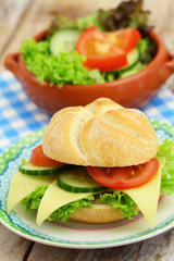 Cheese roll with lettuce, tomato and cucumber and bowl of green salad