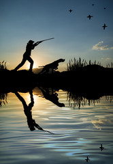Silhouette of woman hunter at sunset. Duck hunting with dogs.
