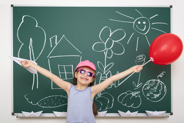girl drawing home and garden on school board