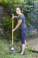 Young woman raking grass in garden