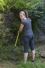 Young woman raking grass in garden