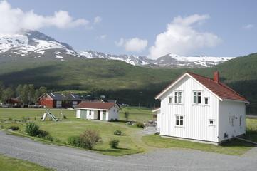белый норвежский дом на фоне зеленых холмов