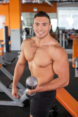 Attractive young athlete is raising dumbbell in gym