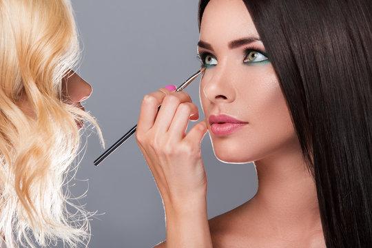 Makeup artist applying eyeshadow on model eyes