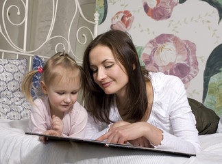 portrait of mother and daughter laying in bed  reading book