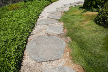 Stone walkway on a grass at the summer park
