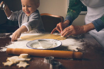 Happy little boy with grandmother cutting  Christmas cookies.