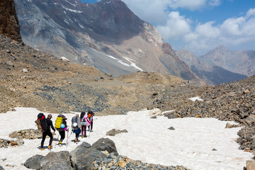 Group of Hikers Walking on Snowfield Alpine Climbers Team Sport Clothing with Heavy Backpacks and Climbing Gear Crossing Snow Place Mountain Landscape Blue Sky Clouds on Background