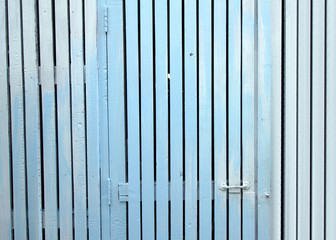 Door panels and a white picket fence with blue.