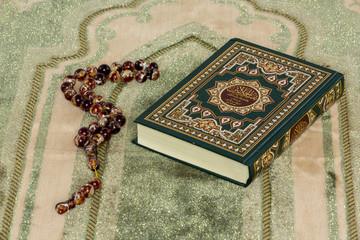 Quran and prayer beads on prayer mat