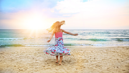 carefree girl dancing on the beach in a dress