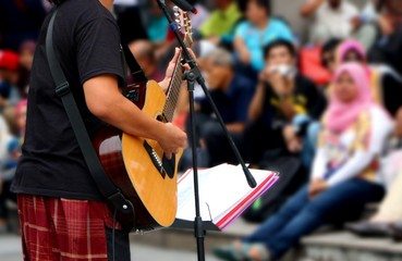 street musician with guitar, with audience in background
