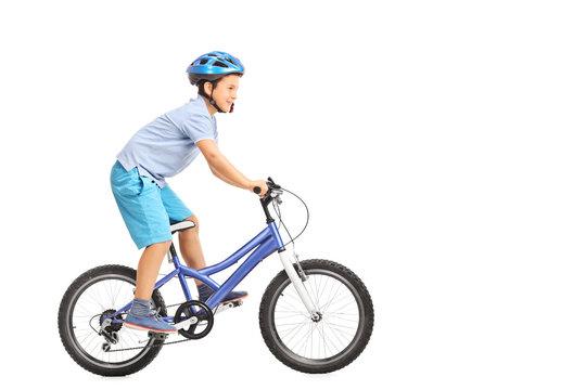 Llittle boy with blue helmet riding a small blue bike isolated o
