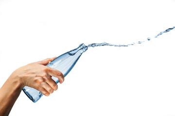 Hand splashing drinking water from glass bottle