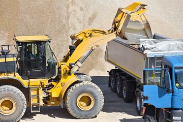 Baumaschinen: Radlader und LKW in einem Kieswerk  - Beladung mit Kies