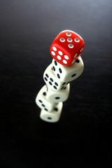One Red game dice on top of stacked five white game dice