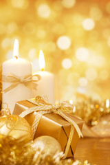 Christmas scene with gold baubles, gift and candles