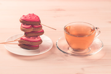 delicious fresh cookies in the shape of a heart on a white plate on wooden background. Cup of green tea. Breakfast