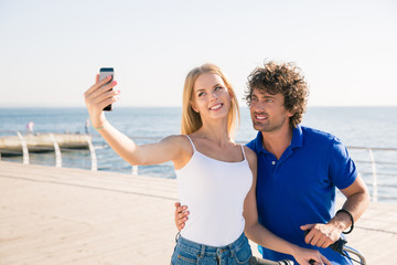 Couple making selfie photo on smartphone outdoors