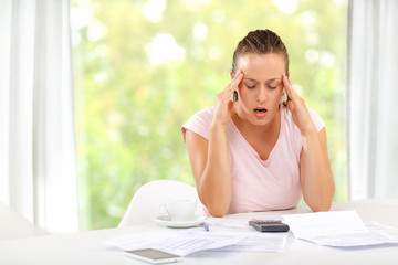 Young woman having a headache over her monthly expenses