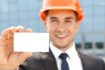 Handsome architect showing business card