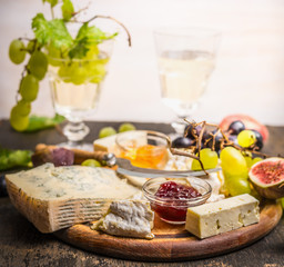 cheese plate with Gorgonzola and Camembert with honey and jam dark and bright grapes glass of wine grapes on a branch inside on dark wooden background close up