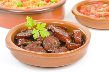 Chorizo al Vino (Spicy sausage cooked in red wine). Traditional Spanish tapas dish. Other tapas dishes on background.