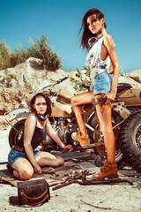Sexy mechanic girls are repairing old motorbike on the desert ba