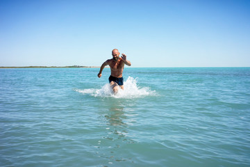 Bald middle-aged man running fast on the sea with a naked torso