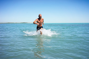 Bald middle-aged man running fast on the lake with a naked torso
