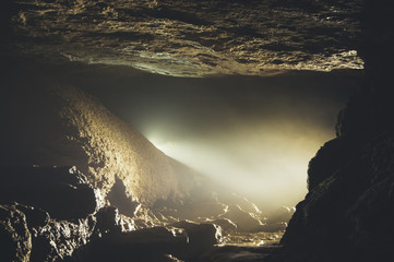 cave entrance with mist and light Wall mural