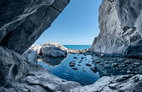 sea cave rocks. Grotto with water reflections
