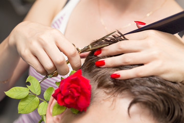 cutting hair with a red rose in a beauty salon