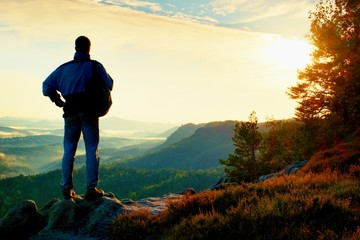 Silhouette of tourist with backpack. Sunny spring daybreak in rocky mountains. Hiker with sporty backpack stand on rocky view point above misty valley.