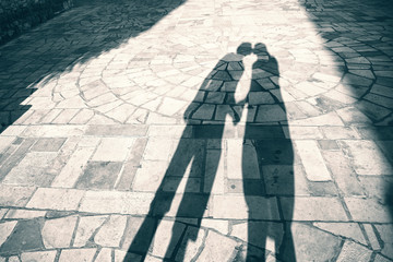 Silhouette shadow of two people holding hands and kissing background, shadow of two adult (girl and boy) holding hands at Sunset light. Blue green color effect effect used.