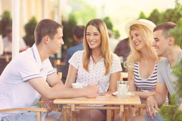 Group of cheerful teenage friends hanging out in a outdoor cafe