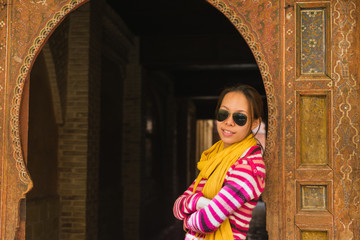 The asian woman stand in front of the wooden gate