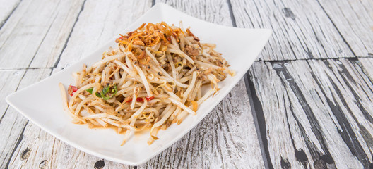 Malaysian dish bean sprout salad or local name Kerabu Taugeh in a white plate over wooden background