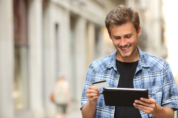 Man buying online with a credit card and a tablet