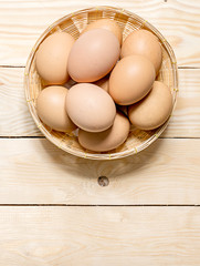 Hen eggs in basket on table