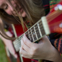 Young girl hand playing on acoustic guitar. Close-up.
